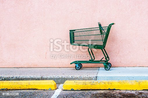 Abandoned Shopping Cart against Pink Wall