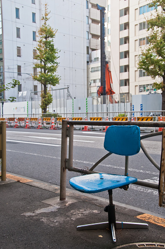 Abandoned simple blue office chair on a street alone in the morning