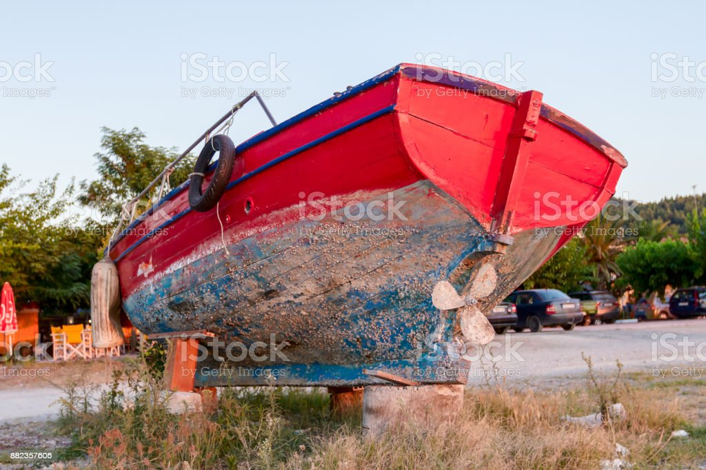 Abandoned small and aged motorboat is dry docked on the beach, weedy junk stock photo