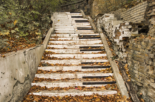 Abandoned stairs, are painted in the style of piano keys surrounded by autumn fallen yellow leaves and collapsed walls. Concept, symbolizing autumn sad music, song or a symphony