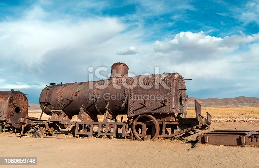 rusty abandoned steam train by bright sunny day near Uyuni town in Bolivia