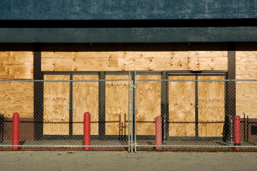 Front view of an abandoned store with boarded windows and fence to keep trespassers out.