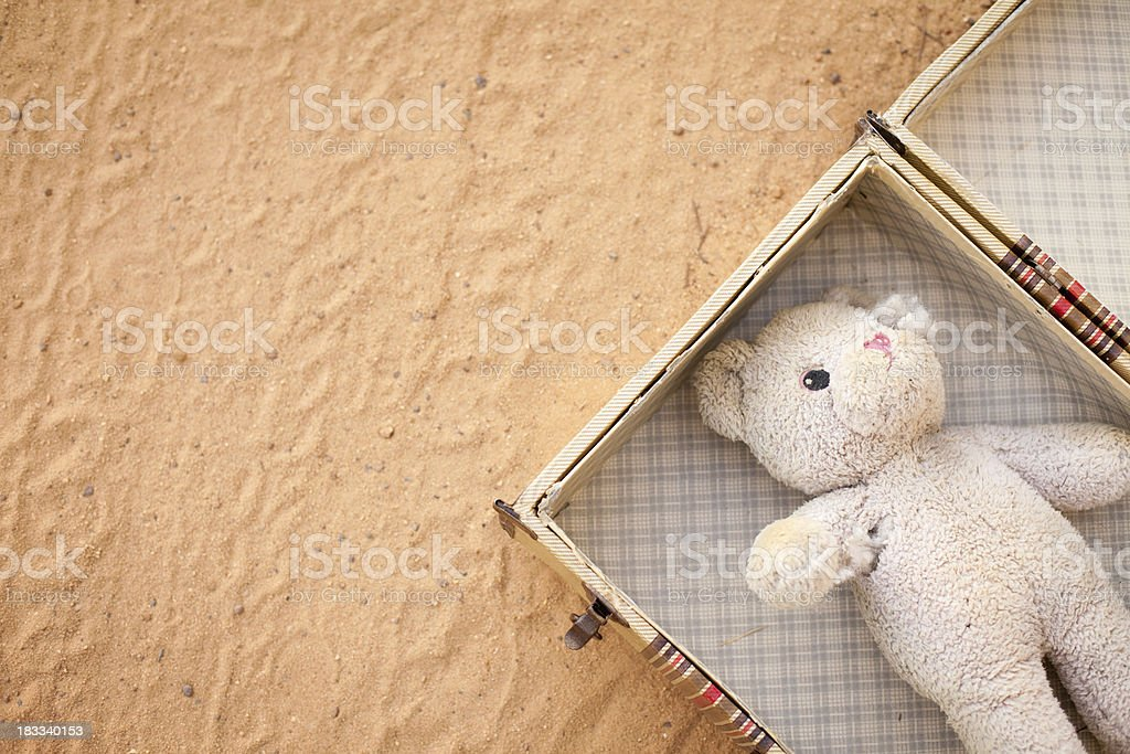 Abandoned Suitcase with Teddy Bear on Dirt Road stock photo