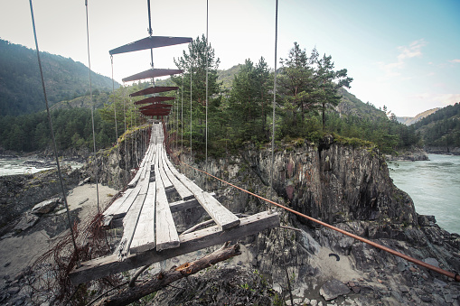 istock Abandoned suspended pedestrian bridge in mountains 911405388