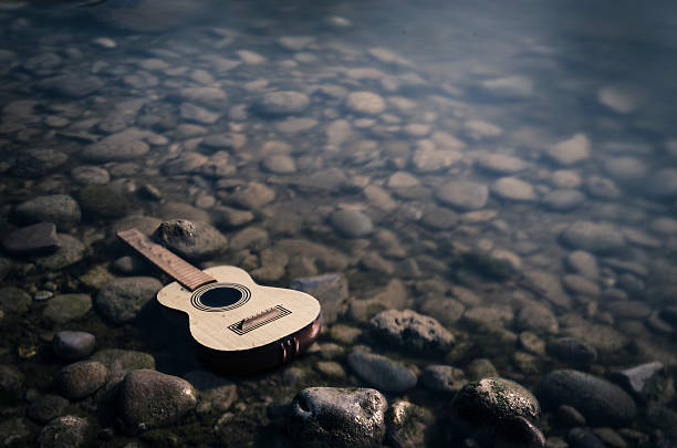 abandoned toy guitar in a river, long exposure foto