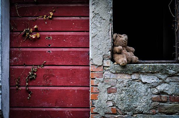 abandoned toy on a broken window foto