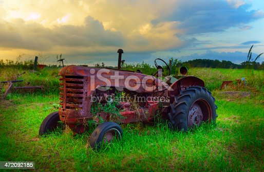 Old abandoned tractor on a farm with storm clouds in the background.