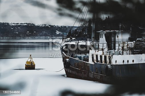 An abandoned trawler moored in an ice-filled cove.