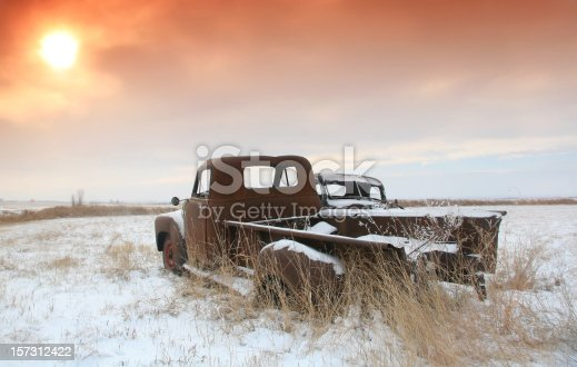 A couple of abandoned vehicles on the plains. Alberta, Canda. Rural winter scenic. Cold winter image of rusty abandoned trucks near Calgary in southern Alberta. A misty haze covers the rugged agricultural terrain and the sun, an orange ball just above the horizon, hides behind the cloud cover. Nobody is in the image.