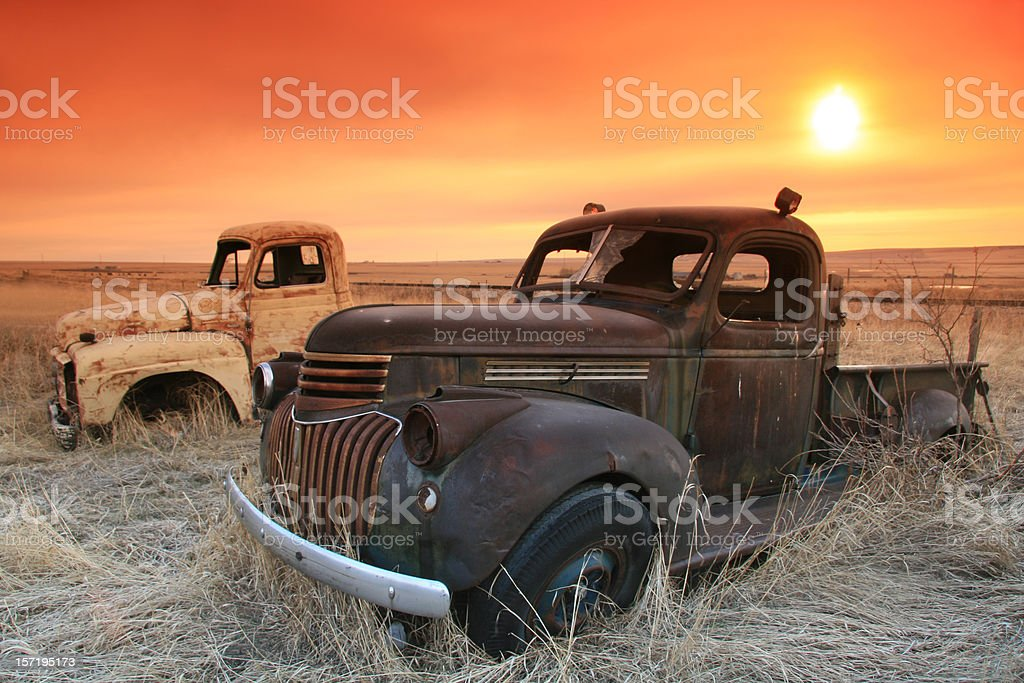 Abandoned Trucks on the Prairie With Sunrise stock photo