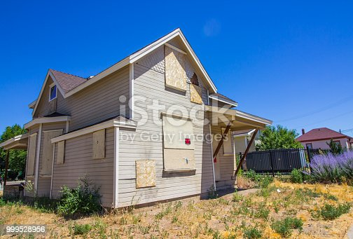 Abandoned Two Story Home With Boarded Up Doors & Windows