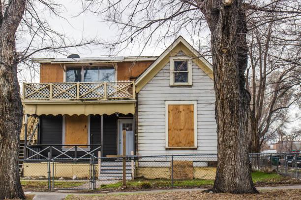 casa abandonada de dos pisos con ventanas tapias - embargo hipotecario fotografías e imágenes de stock