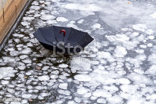 abandoned umbrella on an ice of city river or lake