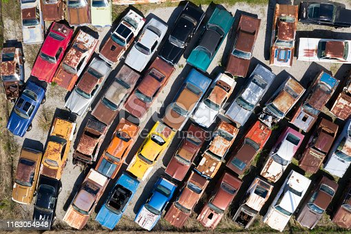 Rows of abandoned vintage American cars from above.