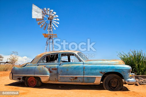 A rusty, abandoned, vintage American car in the desert, Namibia.