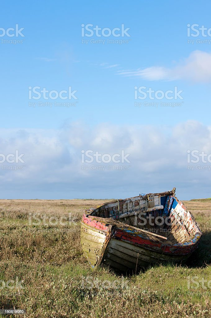 Abandoned weathered wooden rowing boat resting on inland coastal waters royalty-free stock photo