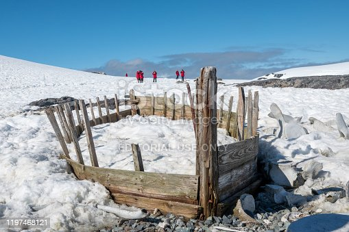 Deception Island, Antarctica - December 17, 2019.  visitors explore an abandoned Norwegian whaling station on Antarctica's Deception Island. In 1911, a permanent station was built to process whale blubber into oil but it closed 20 years later when the whales were wiped out from the area.