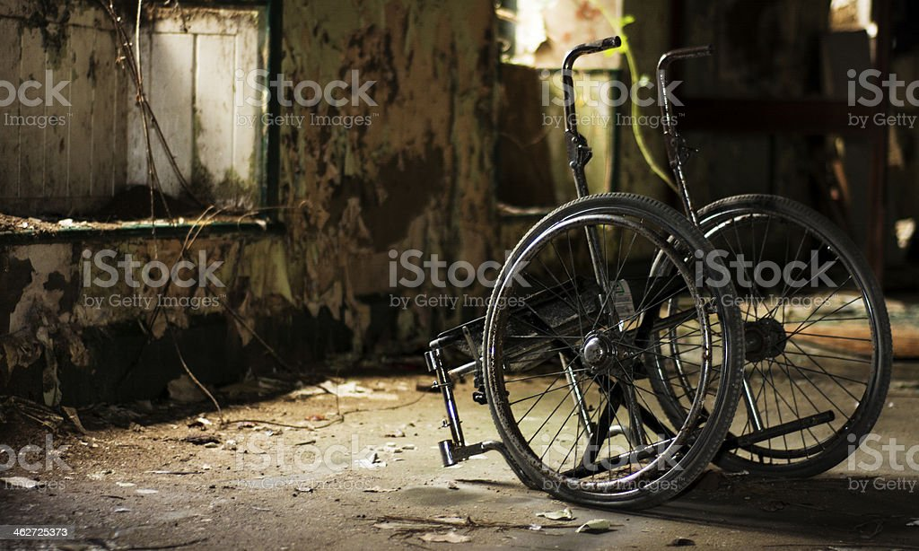 Abandoned wheelchair in derelict building stock photo