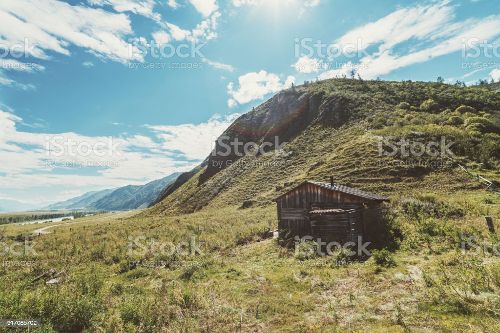 Abandoned wooden shack in mountains stock photo