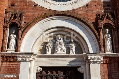 Church of Viboldone, with bell tower, arches, statues and trees during a sunny day in the countryside of Milan.