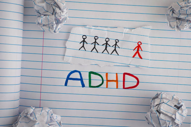 ADHD. Abbreviation ADHD on notebook sheet with some crumpled paper balls on it stock photo
