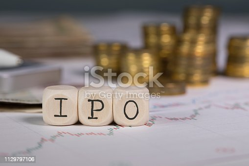 Abbreviation IPO composed of wooden letters. Stacks of coins in the background. Closeup