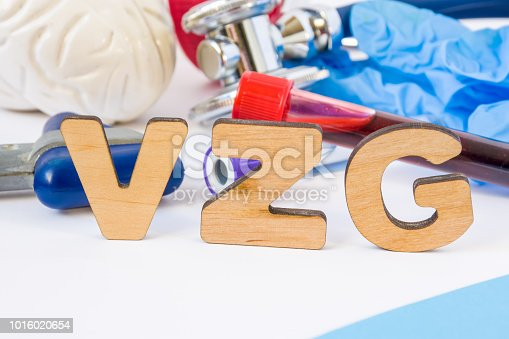 istock VZG abbreviation or acronym in foreground, in laboratory, scientific or medical practice meaning varicella zoster IgG, with model of brain, neurological hammer, laboratory test tubes,  stethoscope 1016020654