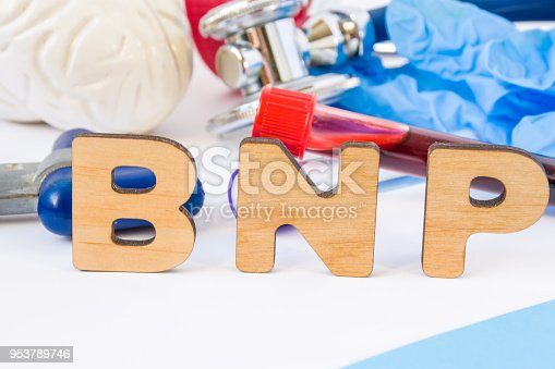 istock BNP abbreviation or acronym in foreground in laboratory scientific or medical practice meaning brain natriuretic peptide, with model of brain, neurological hammer laboratory test tubes 953789746