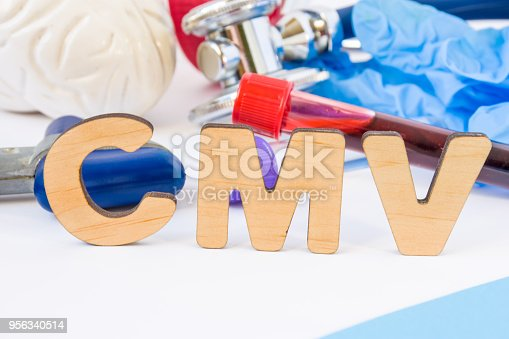 istock CMV abbreviation or acronym in foreground, in laboratory, scientific or medical practice meaning Cytomegalovirus, with model of brain, neurological hammer, laboratory test tubes,  stethoscope 956340514