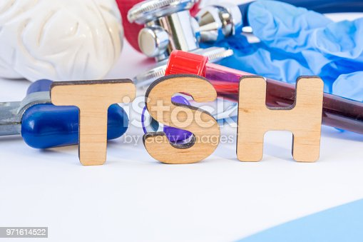 istock TSH abbreviation or acronym in foreground in laboratory scientific or medical practice meaning thyroid stimulating hormone, with model of brain, neurological hammer, laboratory test tubes, stethoscope 971614522