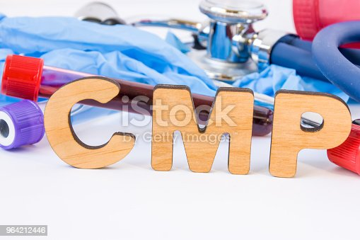 istock Abbreviation or acronym of CMP, in laboratory, scientific, research or medical practice means comprehensive metabolic panel, is in foreground with laboratory test tubes, medical stethoscope and gloves 964212446