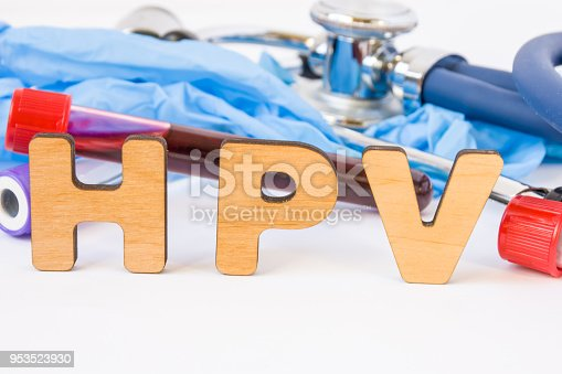 istock Abbreviation or acronym of HPV, in laboratory, scientific, research or medical practice means human papilloma virus, is in foreground with laboratory test tubes, medical stethoscope and gloves 953523930