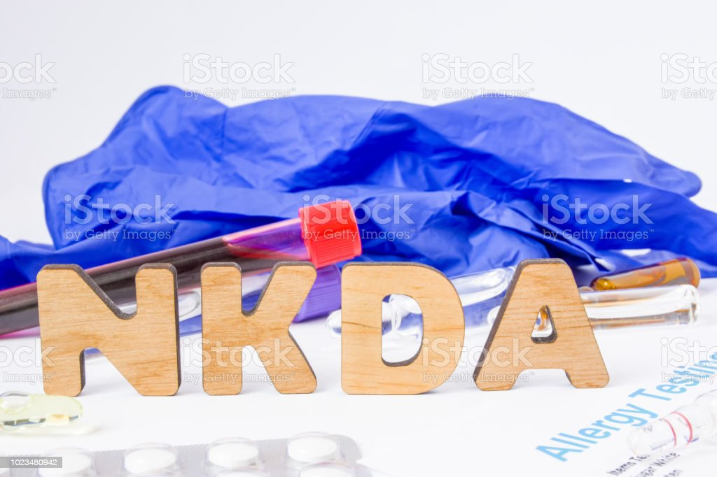 NKDA abbreviation or acronym of no known drug allergies allergic pharmacological response without determining cause. Word NKDA near drugs in form of pills and ampoules, blood sample and allergic test stock photo