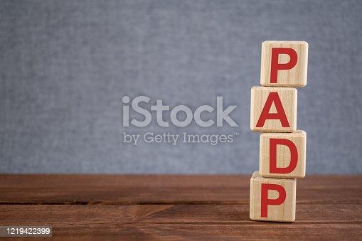istock Abbreviation PADP (pulmonary artery diastolic pressure) text acronym on wooden cubes on dark wooden backround. Medicine concept. 1219422399