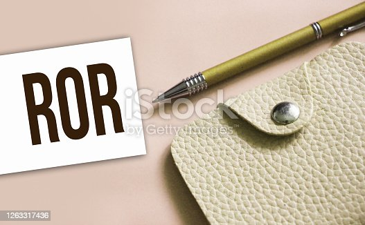 ROR abbreviation written on a business card, pen and beige leather wallet. Financial business concept.