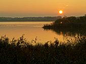 Der Chiemsee ist der größte See in Bayern in Deutschland. Dieses Bild besticht besonders durch den Aufbau mit dem Schilf im Vordergrund. Das goldene Abendlicht wirkt besonders.