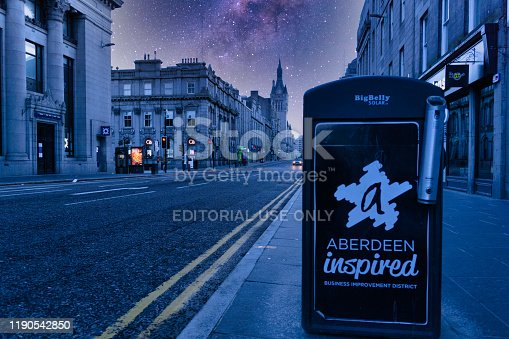 Aberdeen, Scotland, UK - February 10 2019:  Aberdeen is the 3rd largest city in Scotland renowned for it's 19th century architecture and granite buildings.  This has earned it the byname 'The Granite City'.  Here we see Union Street at night, which is the main thoroughfare with the Milky Way visible above.  In the foreground a garbage can advertising a local organisation 'Aberdeen Inspired'.