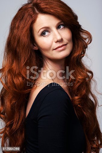 Studio shot of a young woman with beautiful red hair posing against a gray background