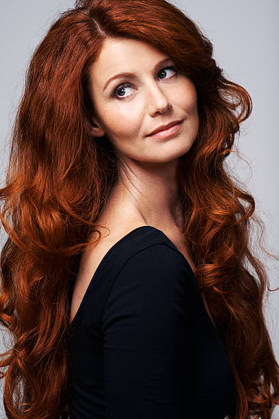 Ablaze with beauty Studio shot of a young woman with beautiful red hair posing against a gray background ablaze stock pictures, royalty-free photos & images
