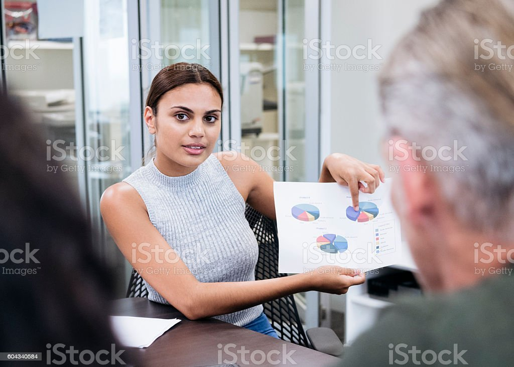 Aboriginal Australian businesswoman showing pie charts in meeting – Foto