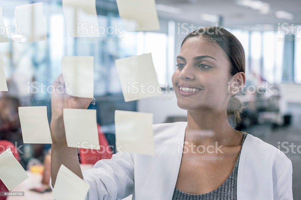 Aboriginal Australian businesswoman smiling, using sticky notes stock photo