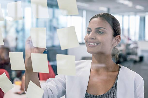 Aboriginal Australian businesswoman smiling, using sticky notes stock photo