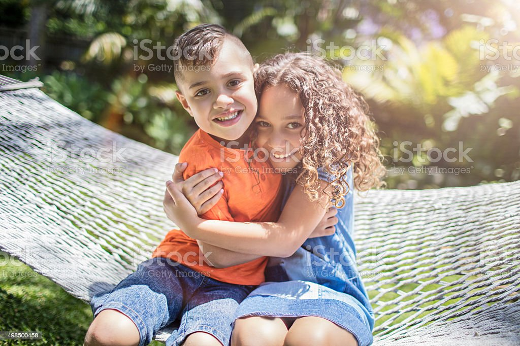 Aboriginal australian siblings hugging in the garden stock photo