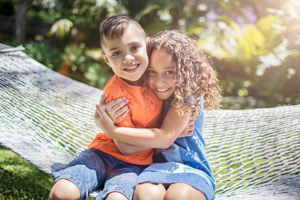 aboriginal australian siblings hugging in the garden - sister stock photos and pictures