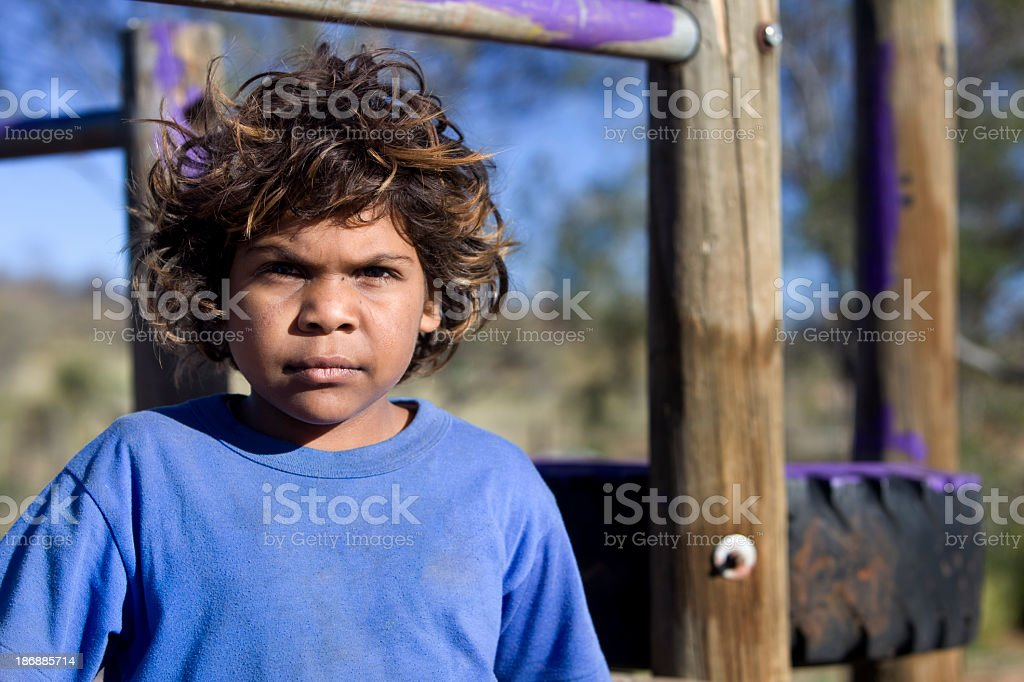 Aboriginal child standing against wooden playground stock photo