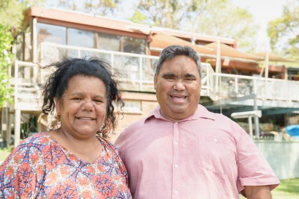 Aboriginal couple smiling toward camera outside house stock photo