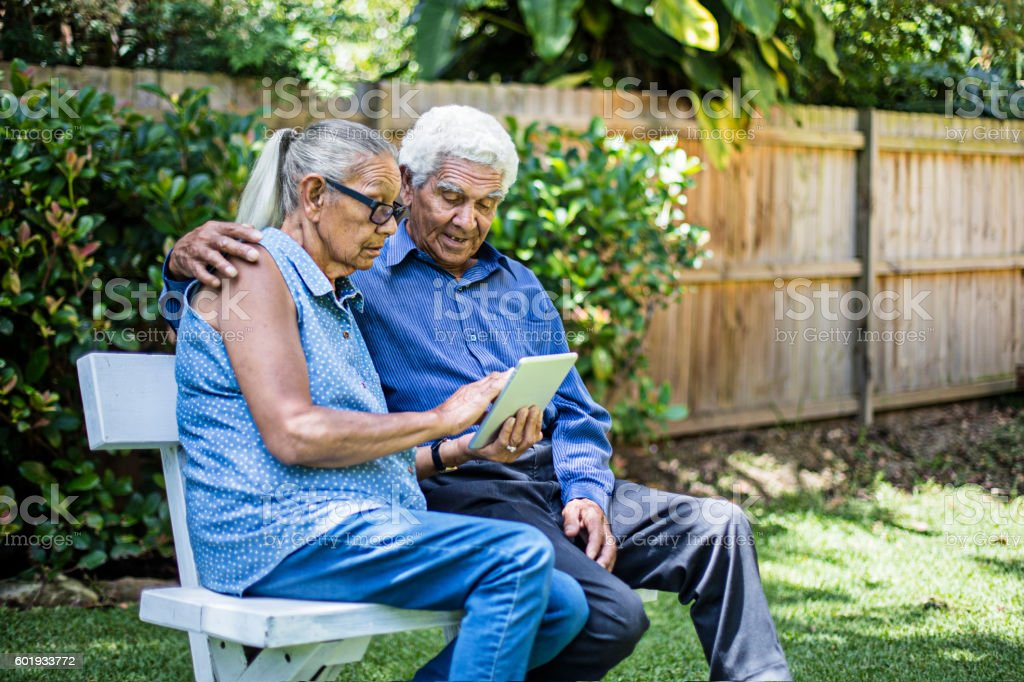 Aboriginal couple using the digital tablet in the garden stock photo