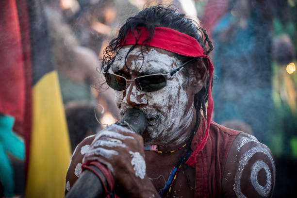 aboriginal elder plays a didgeridoo at mardi grass - didgeridoo stock photos and pictures