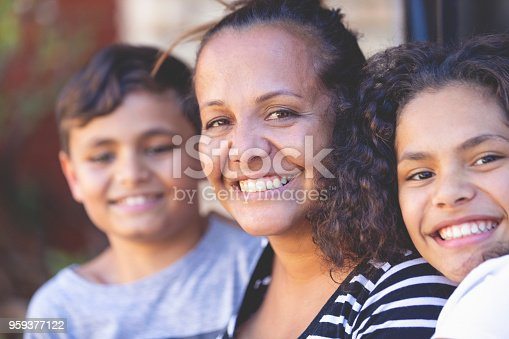 Aboriginal Family portrait with 1 parent and 2 children. They are sitting on the front porch. Everyone is happy and smiling. Could be a single mother.