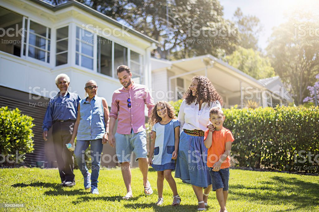 Aboriginal family walking in the garden at home stock photo